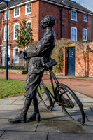 """Sir Edward Elgar leaning on his Sunbeam bicycle - nicknamed Mr Phoebus"", by Jemma Pearson, Hereford Cathedral Close, unveiled in 2005."